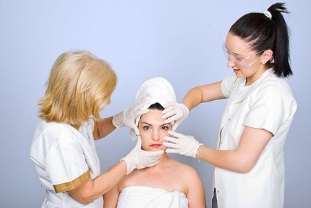 Two plastic surgeons women  examine young woman skin  and holding their hands with rubber gloves on face photo
