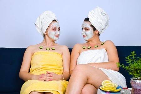 Two beautiful friends woman sitting on couch at spa salon with facial mask and slices cucumber on their chest ,they having an conversation and looking each other and smile photo