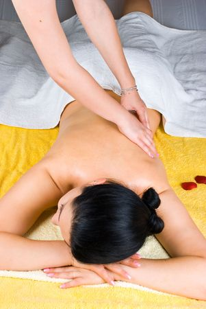 Person massaging woman back at spa resort photo