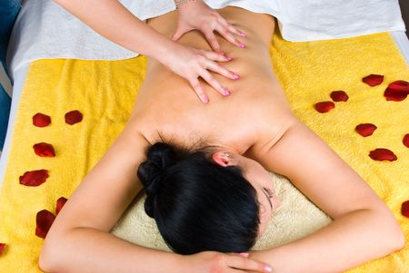 Young woman receiving a professional back massage at spa salon photo