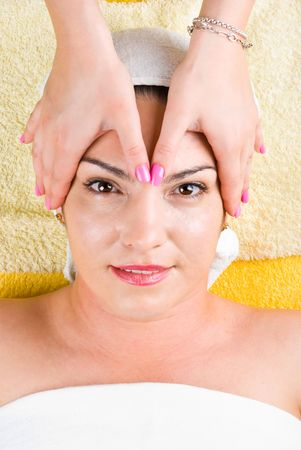 Beautiful 30s woman receiving a head massage at spa salon photo