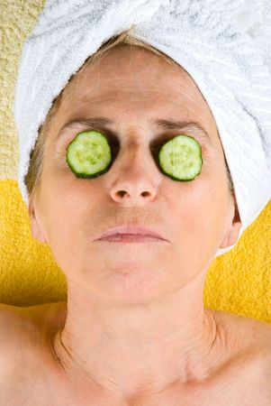 Aged woman lying on table at spa resort and holding slices cucumber on her eyes Stock Photo - 7065427