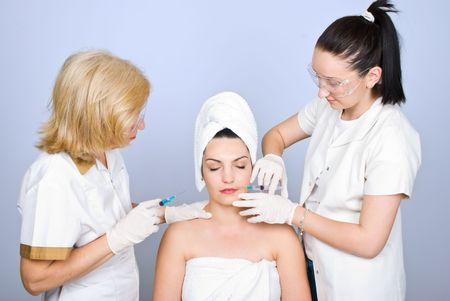 operation: Two plastic doctors giving botox shot to a young woman