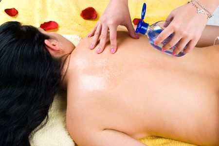 Beautician pouring aromatic massage oil with levander on woman back at spa salon photo