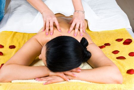 Beautician giving a back massage to a young woman at spa salon photo
