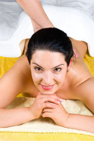 Smiling brunette woman enjoying a bacck massage at spa and sitting with hands under chin photo