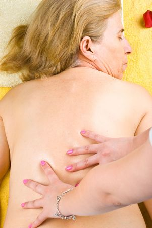 Mature woman getting back massage at spa salon photo