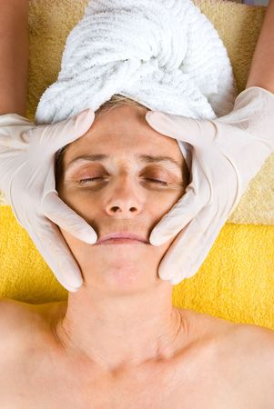 Senior woman having a cosmetic treatment at spa salon and a beautician holding hands in rubber gloves on her face Stock Photo - 7065448