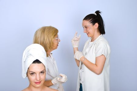 Young woman in front of camera waiting for botox procedure while two doctors having a conversation in background photo