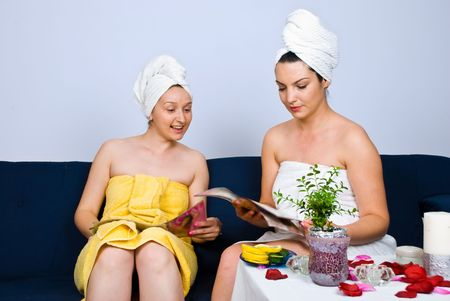 Two beautiful women sitting on couch in waiting room at spa resort and reading magazines Stock Photo - 7097812