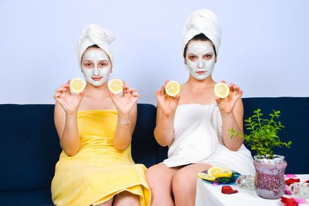 Two women with facial mask showing slices lemon and sitting on couch in waiting room at spa photo
