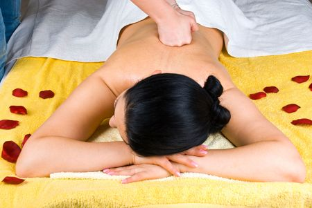 Beautician giving deep back massage to a young woman Stock Photo - 7125392