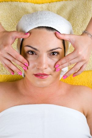 Young woman getting a facial massage at spa photo