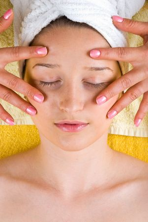 Woman getting a skin eyes facial massage from a beautician at spa photo