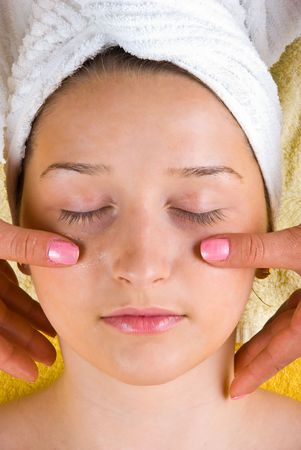 Beauty young woman receiving a facial massage at spa resort photo