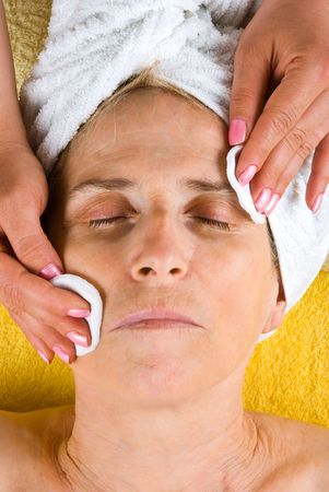 retreat: Senior woman getting a cleansing face at spa retreat