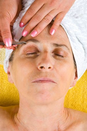 plucking: Senior woman getting plucking eyebrow at salon