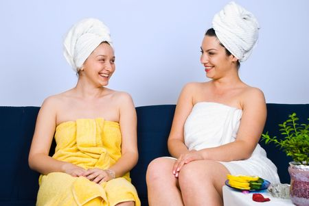 Two woman sitting on couch in a spa  salon waiting room and having a funny conversation and laughing together Stock Photo - 7157538