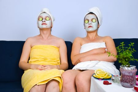 retreat: Two women sitting on sofa at spa retreat and having facial masks on face and slices cucumber on eyes