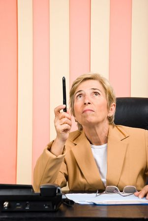 Senior business woman in office looking and pointing up with her pencil photo