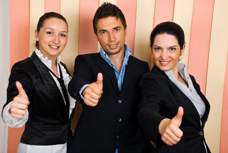 Three  young business people in a row giving thumbs up and smiling photo
