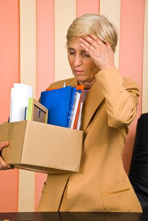 retiring: Fired or retiring woman carrying a box with her belongings and being stressed or worried Stock Photo