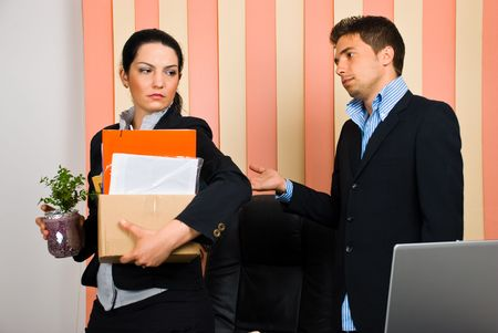 fired: Business woman is dismissed  by her boss and invited to leave the office with her assets in a carton box