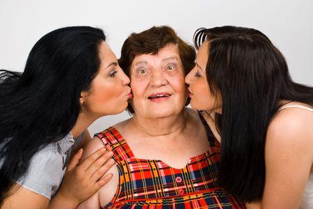 Surprised grandma is kissed by her granddaughter on cheeks photo