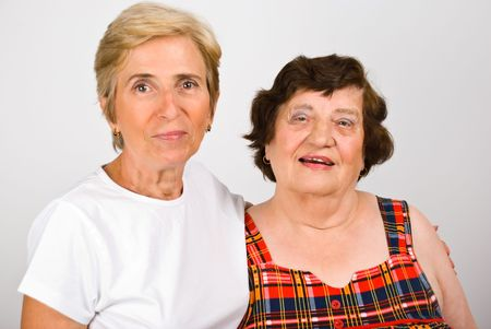 adult 80s: Close up of elderly mother and her mature daughter standing in embrace and smiling together Stock Photo