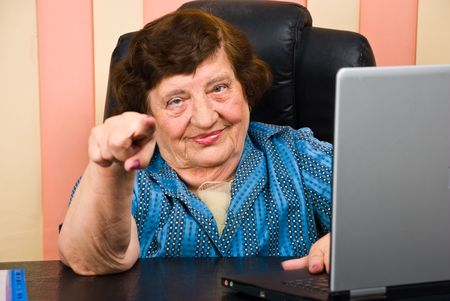 Elderly  business woman sitting on chair at desk in office and pointing to you:Yes,you! photo