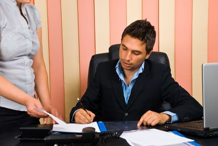 Boss sitting on chair in office signing  his secretary documents photo