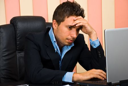 Stressed businessman in an office sitting on chair with hand on forehead and browsing internet on laptop Stock Photo - 7168942