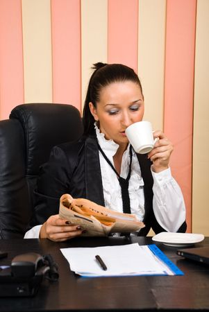 Young business woman drinking coffee and read the news in newspaper  at office in the morning photo