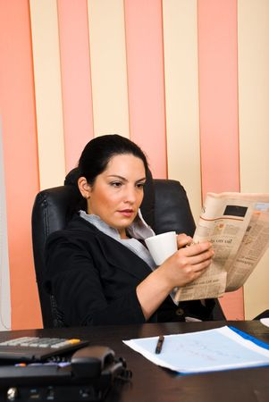 Young business woman sitting comfortable in her chair at office,drinking a cup of coffee and reading a newspaper photo