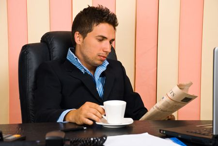 Serious business man reading a newspaper and drinking a cup of coffee in his office photo