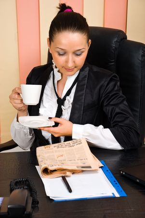 Young businesswoman reading the news in newspaper and drinking coffee in her office photo