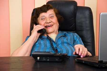 Senior business woman having a funny conversation by telephone and she laughing photo