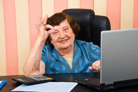 Cheerful elderly executive woman showing okay sign hand and smiling in her office photo
