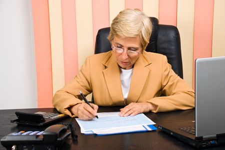 Consultant woman with glasses sitting at desk in office and working on some financial graphs photo