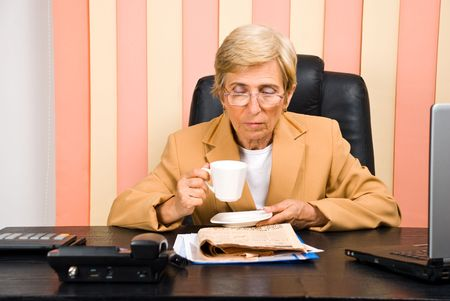 Senior executive woman with glasses reading news and drinking coffee photo