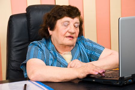 Older business woman in office using laptop  photo
