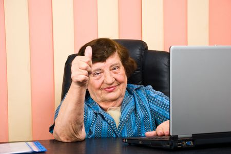 Older corporate woman giving  thumbs up and sitting at desktop photo