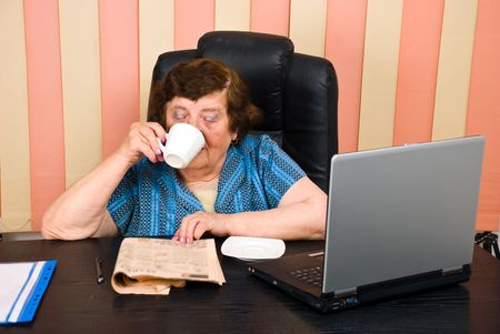 Elder executive woman reading news and drinking coffee at office photo