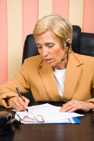 Senior sales representative woman taking notes and working photo