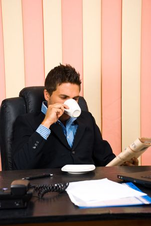 Corporate man reading news and drinking coffee at office photo