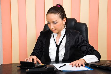 Young business woman using calculator in her office photo