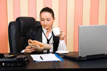 Business woman sitting comfortable in her chair in office reading newspaper and drinking coffee photo