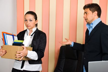fired: Disappointed woman  holding box with  belongings is fired by her boss and invited to leave the office
