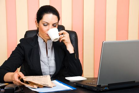 Corporate woman reading news and drinking coffee in her office photo
