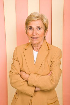 mani incrociate: Donna bionda senior business in piedi con le mani incrociate e sorridente  Archivio Fotografico